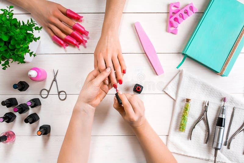 关心棉花取消拖把油漆的指甲盖钉子 归档与专业指甲锉的女性手特写镜头钉子在秀丽钉子沙龙 顶视图 免版税库存图片