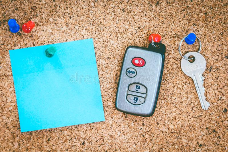关键持有人房子和遥远的汽车钥匙在黄柏上 免版税图库摄影