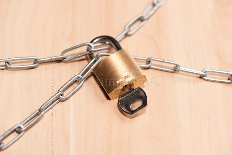 关键锁锁与在桌上的一个链子 图库摄影