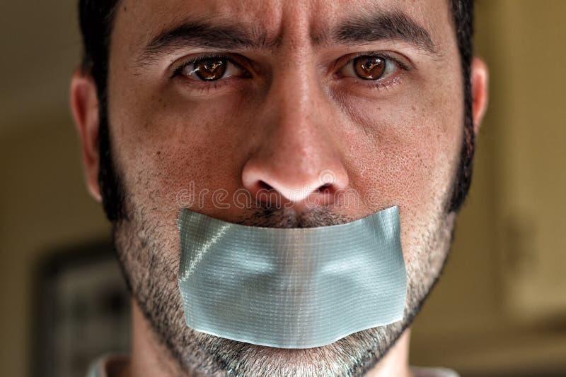 关闭一个人的画象有胶带的在他的嘴 库存图片
