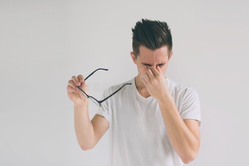 关闭一个可爱的人的画象有镜片的 可怜的年轻人有眼力问题 他磨擦他的鼻子和 免版税库存照片