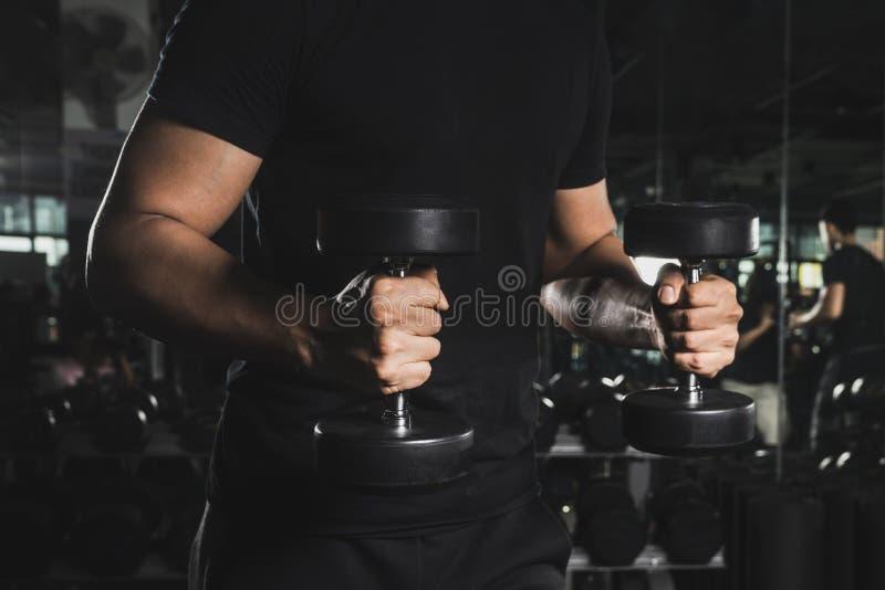 关闭一个在健身房的肌肉年轻人举的重量在黑暗的背景 免版税库存照片