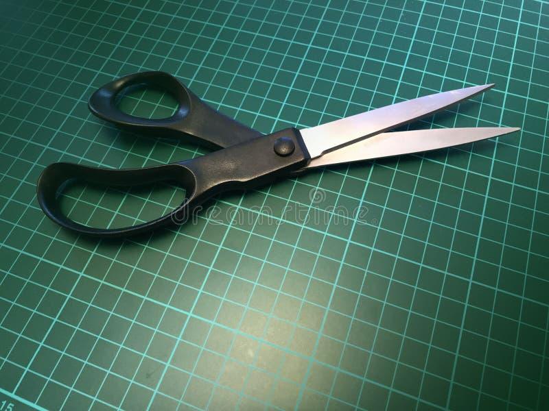 关闭一个对不锈钢在切口席子的金属剪刀 免版税库存图片