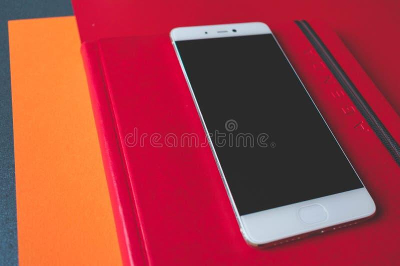 关闭一个手机和一个笔记本的红色皮革盖子有在盖子写的议程的 免版税库存图片