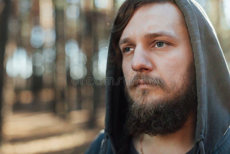 关闭一个有胡子的行家游人的画象灰色敞篷人的在阳光森林森林里 库存照片