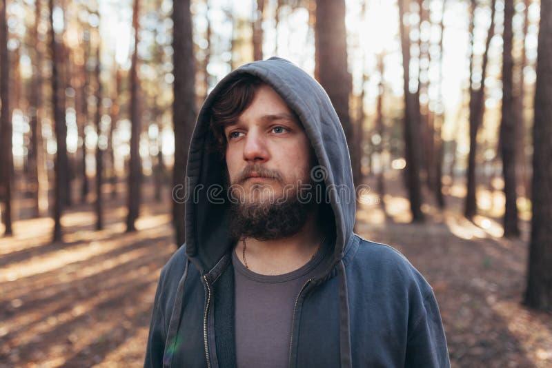 关闭一个有胡子的行家游人的画象灰色敞篷人的在阳光森林森林里 图库摄影