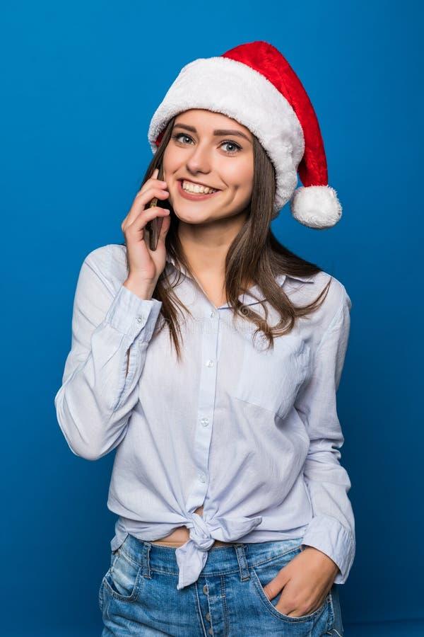 关闭一个爽快相当十几岁的女孩的画象圣诞老人帽子的谈话在手机被隔绝在蓝色背景 免版税图库摄影