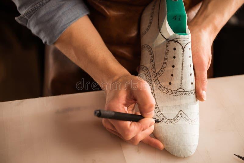 关闭一个男性鞋匠图画设计 免版税库存照片