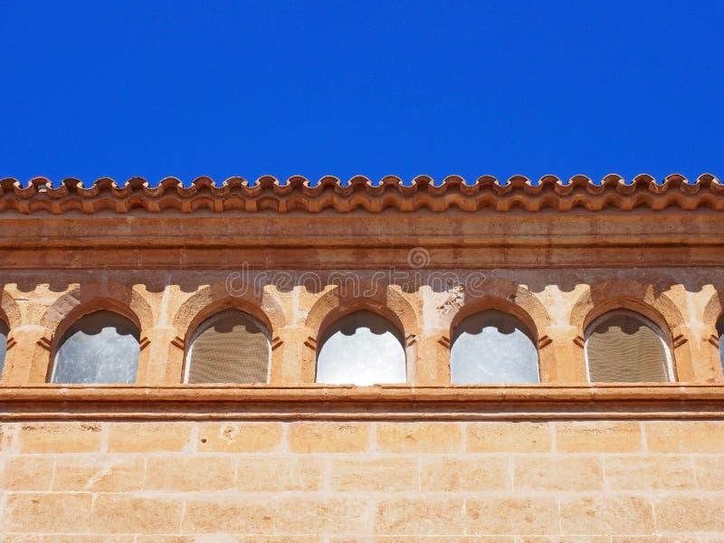 关闭一个老石西班牙大厦的屋顶线与弯曲的瓦片和华丽窗口的与明亮的蓝色被日光照射了天空 库存图片