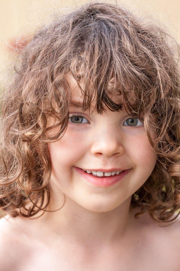 关闭一个逗人喜爱的俏丽的微笑的学龄前女孩的夏天画象 图库摄影