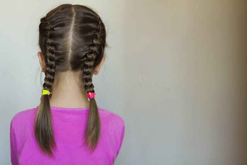 关闭一个逗人喜爱的小女孩的后方vew画象有滑稽的猪尾的在白色背景 时尚和愉快的童年 免版税库存照片
