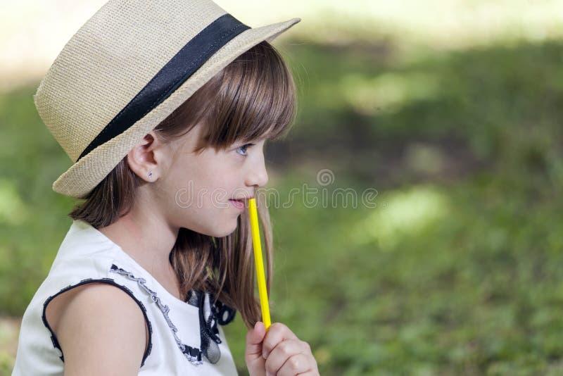 关闭一个逗人喜爱的小女孩的画象有帽子的在公园 免版税库存照片