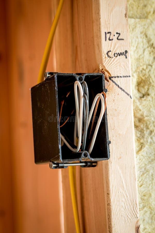 关闭一个黑塑料电子箱子登上对有被暴露的导线的墙壁 图库摄影