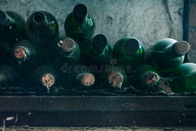 关闭一些非常老和多灰尘的酒瓶在葡萄酒库里 库存图片