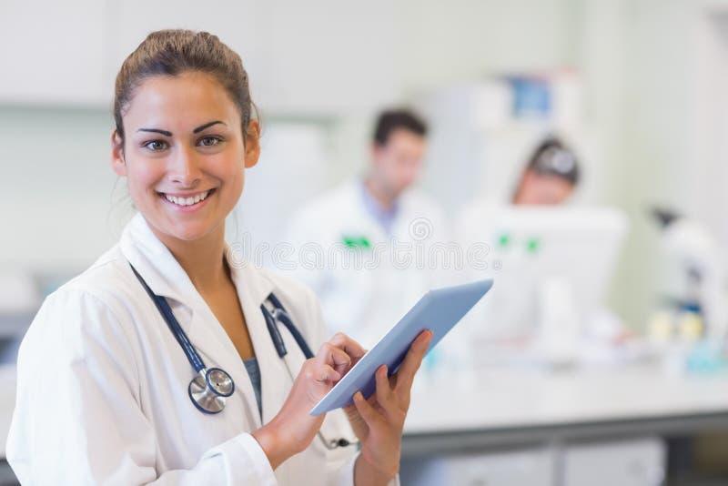 关闭一位女性医生的画象有片剂个人计算机的 免版税库存照片