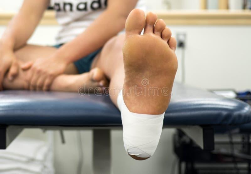 关闭一只女运动员` s脚的底视图在脚腕磁带工作的从桌的底部 免版税图库摄影