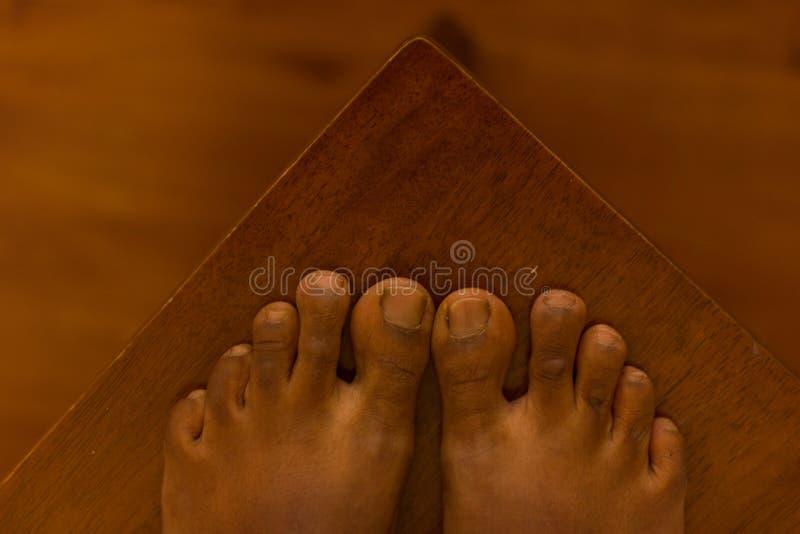 关闭一只棕色亚洲脚,在与Mortons脚趾的棕色木背景 免版税图库摄影