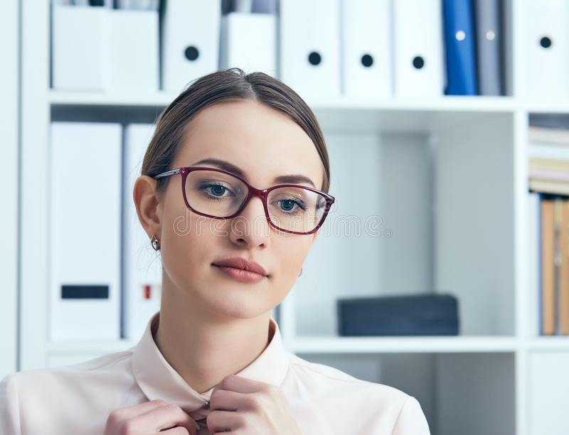 关闭一名体贴的女实业家的画象装饰在调查距离的运作的衣服在办公室 免版税图库摄影