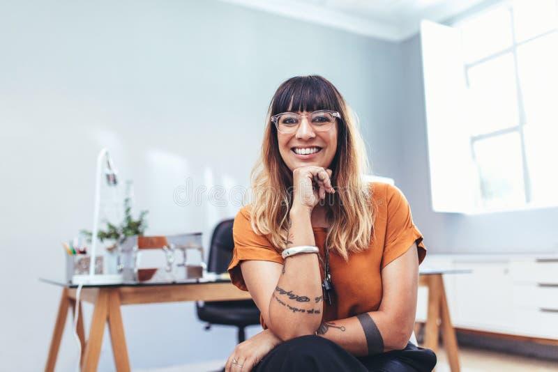 关闭一名微笑的女实业家在办公室 免版税库存照片
