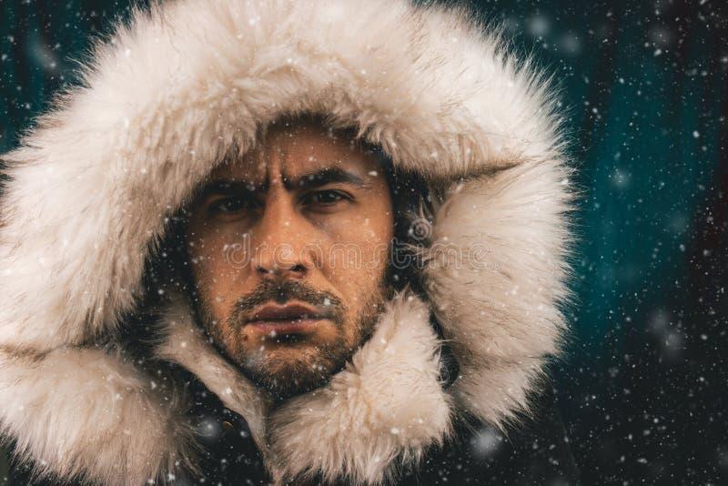 关闭一名白人的画象打扮与在雪的一件爱斯基摩夹克 免版税图库摄影