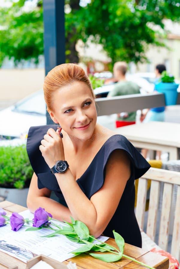 关闭一名美丽的聪明的妇女的画象有明亮的红色头发的 一件黑礼服的时髦的女孩在a.c.大阳台  免版税库存图片
