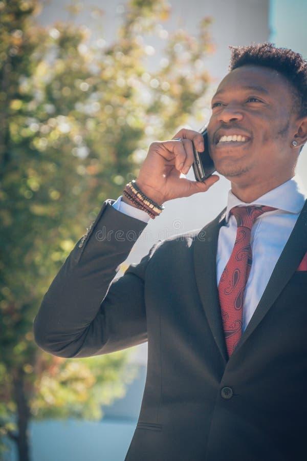 关闭一年轻和可爱的黑商人审阅一条行人交叉路和谈话用在a前面的电话 库存图片