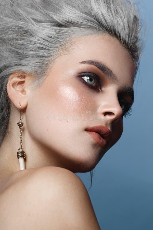 关闭一年轻女人,smokey眼睛,构成,赤裸肩膀的画象有灰色发型的,在蓝色背景 免版税库存照片