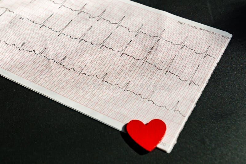 关闭一张心电图在纸形式vith红色木心脏 在黑背景的ECG或EKG纸 医疗和 库存照片