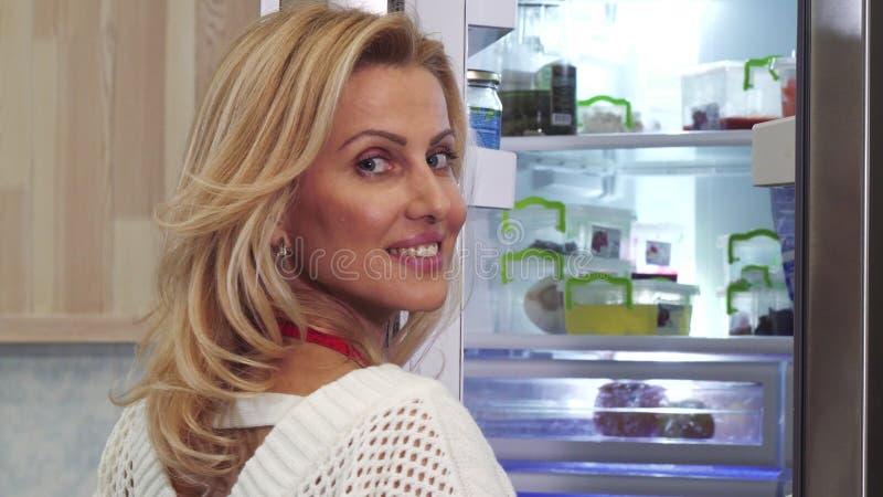 关闭一美丽的妇女微笑的看在冰箱 免版税库存照片