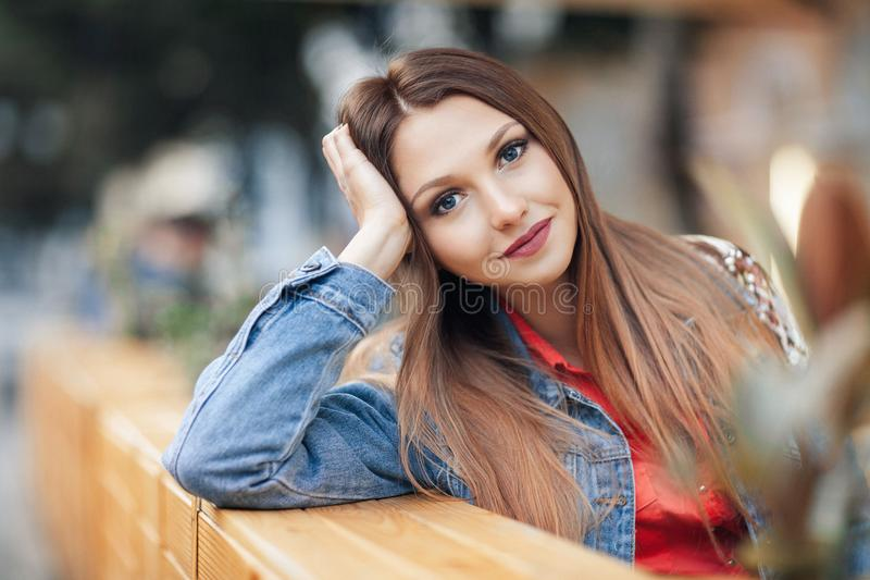 关闭一美好白肤金发女孩手倾斜面孔坐的画象室外在舒适咖啡馆在镇里 相当看加州的年轻模型 免版税库存照片