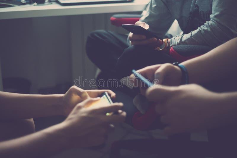 关闭三个对年轻千福年的少年的手使上瘾对一起使用与智能手机的技术在线 免版税库存照片