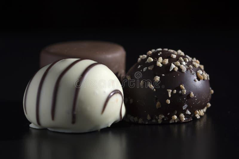 关闭三个巧克力糖果、白色黑暗和牛奶巧克力 与不健康和fa的甜,卡路里丰富和能源丰富食物 库存照片