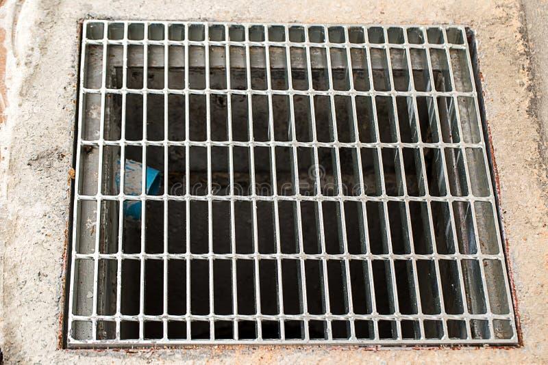 关闭下水道格栅流失在街道或走道附近 库存照片