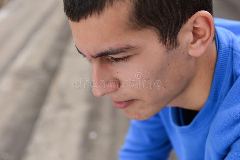 关闭不快乐的少年学生外面坐stadiu 库存图片