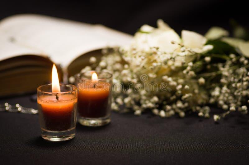 关闭与一个被弄脏的念珠小珠的两个橙色蜡烛在一朵圣经和小花,黑背景 免版税库存照片