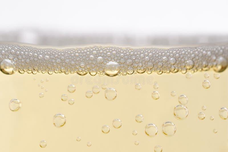 关闭与上升的泡影的被填装的香宾玻璃 免版税库存图片