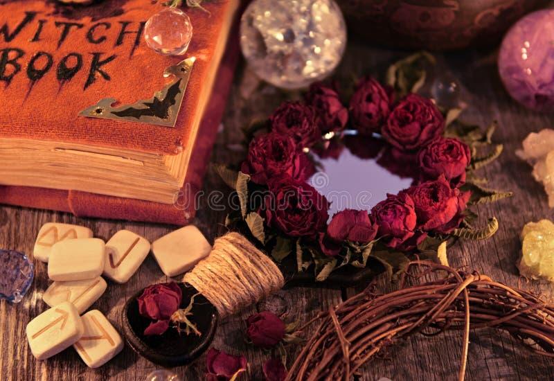 关闭与不可思议的镜子、巫婆书和诗歌在桌上 隐密,神秘和占卜静物画 库存图片