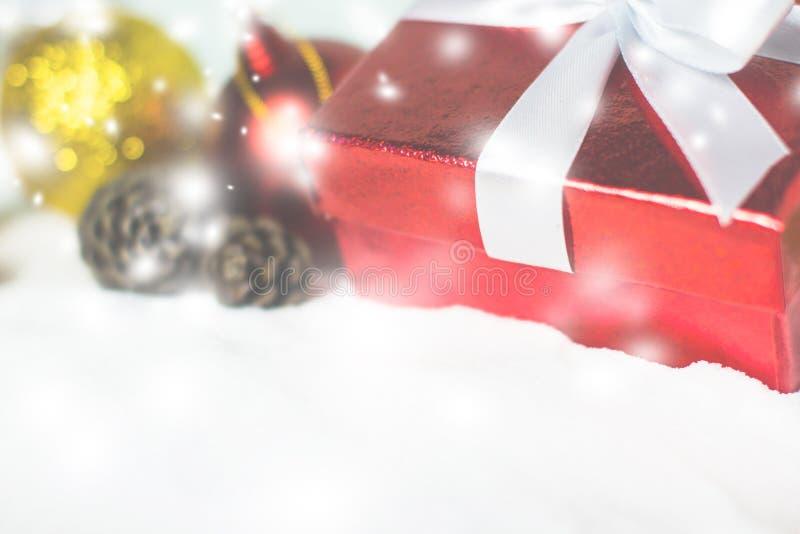 关闭与圣诞节球和杉木的红色礼物盒白色丝带 库存图片