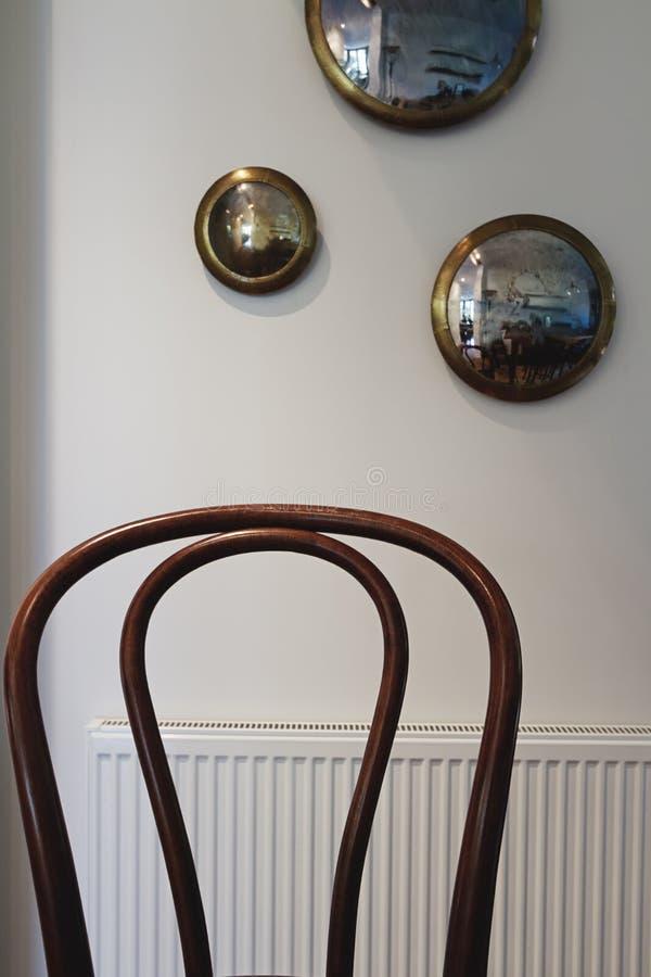 关闭与墙壁装饰和radiat的木葡萄酒椅子 免版税库存照片