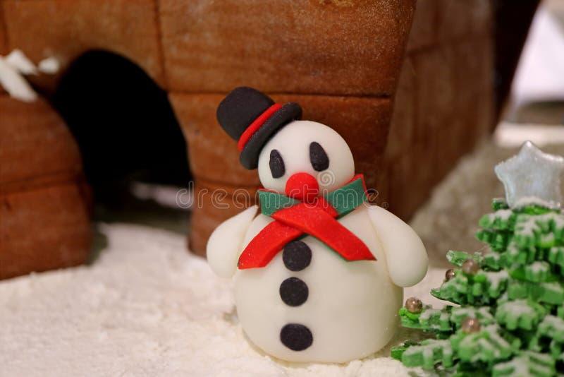 关闭与姜面包议院和糖果圣诞树的逗人喜爱的雪人小杏仁饼 免版税图库摄影