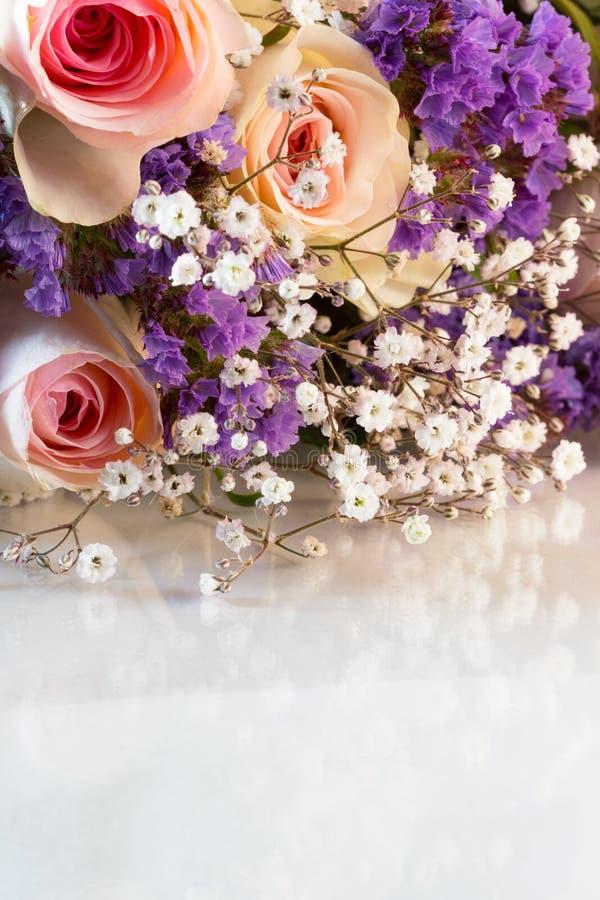 关闭与小紫色和白花混合的桃红色玫瑰花束  库存照片