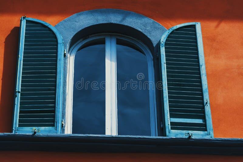 关闭与开放快门的一个窗口在橙色墙壁上 免版税库存图片