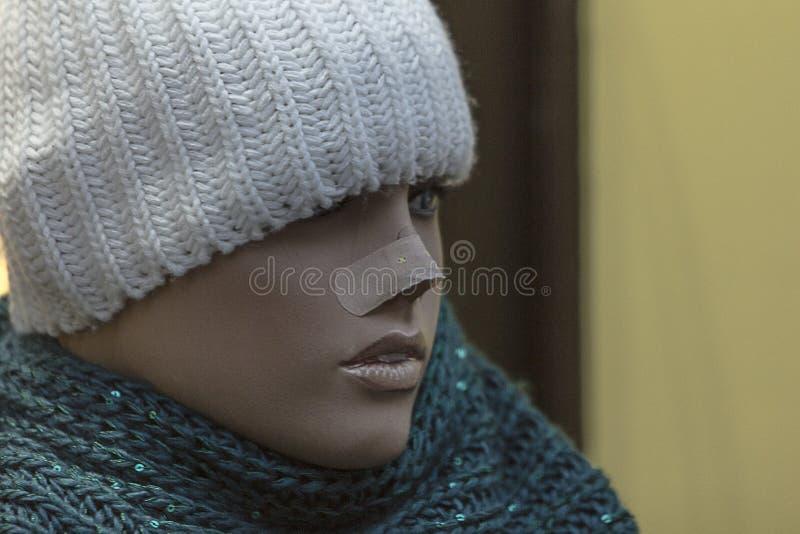 关闭与急救带的一个假的妇女时装模特在鼻子、被编织的盖帽和围巾 与拷贝空间的外形视图 免版税库存照片