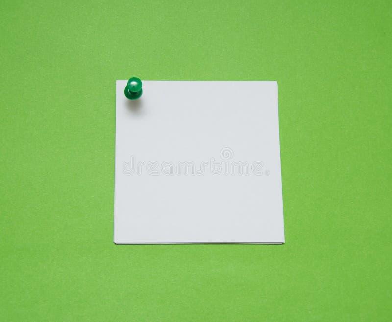关闭与推挤别针的一张便条纸在绿色背景 图库摄影