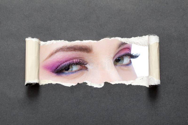 关闭与明亮的构成的女性眼睛在灰色被撕毁的纸 库存图片