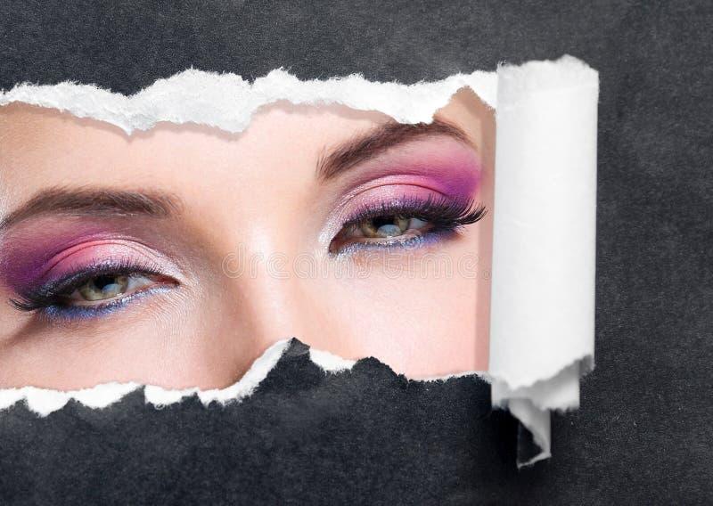关闭与明亮的构成的女性眼睛在被撕毁的黑纸 库存照片