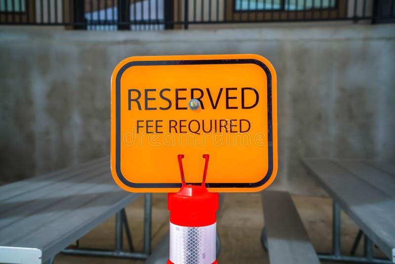 关闭与桌和长凳的橙色后备的标志在背景中 免版税库存图片