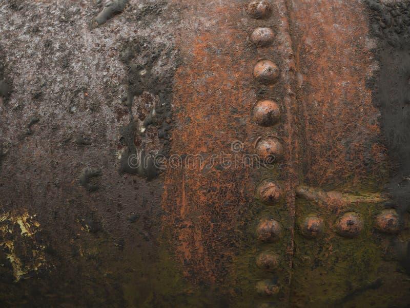 关闭与桶盖的一条生锈的棕色和橙色钢水管线和剥皮颜色 工业抽象纹理 免版税库存图片
