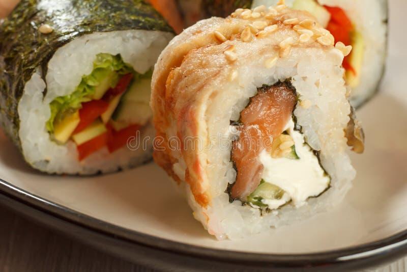 关闭与海鳗之类的Uramaki 与nori,米,鳗鱼f的寿司卷 免版税库存照片