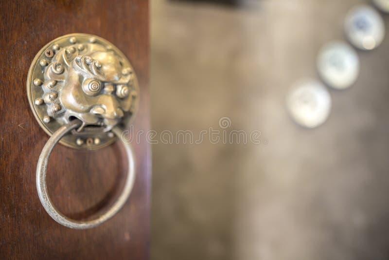 关闭与狮子头的黄铜古铜色中国传统通道门环 库存照片